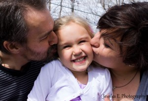 Parents kiss their daughter on the cheek.